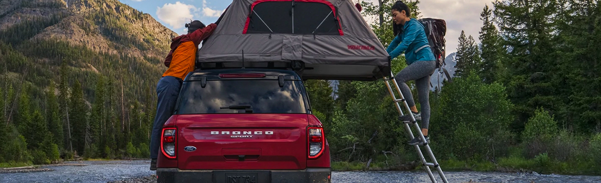 Two people setting up a rooftop tent on a 2021 Ford Bronco Sport