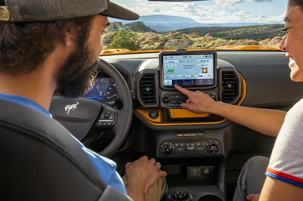 Two people using the eight inch touchscreen in a 2021 Ford Bronco Sport